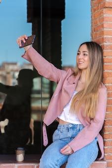 Młoda kobieta fotografuje się z telefonem komórkowym oparty o okno