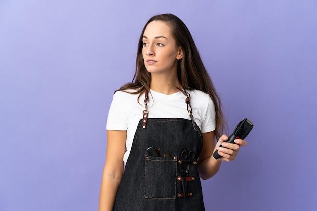 Młoda kobieta fryzjer na białym tle patrząc z boku