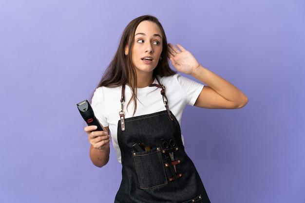 Młoda kobieta fryzjer na białym tle słuchając czegoś, kładąc rękę na uchu