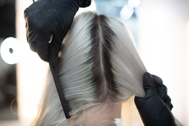Młoda kobieta fryzjer umiera włosy w salonie kosmetycznym. profesjonalne farbowanie cebulek włosów