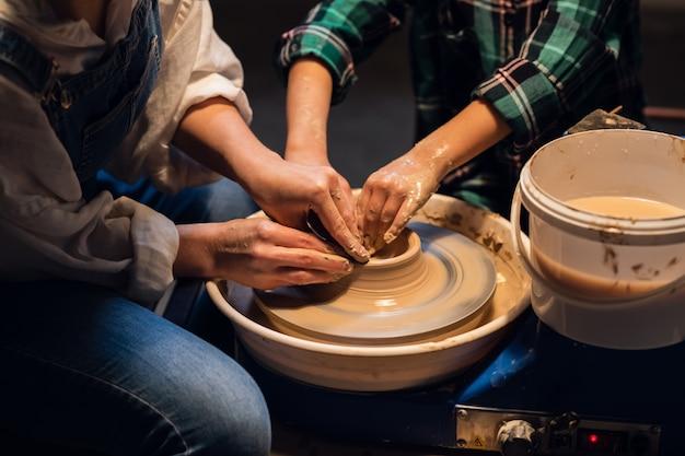 Młoda kobieta-garncarz uczy małego chłopca, jak zrobić garnek z gliny.