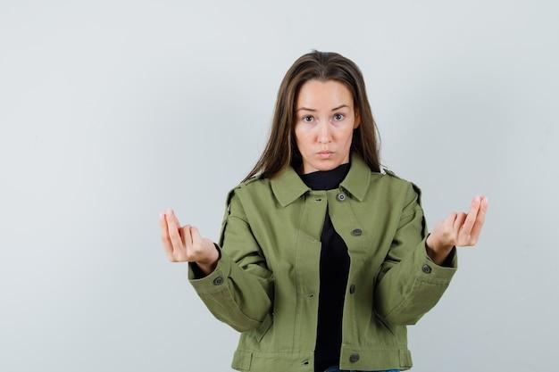 Młoda kobieta gestykuluje jak wyjaśniać coś w widoku z przodu zielonej kurtki.