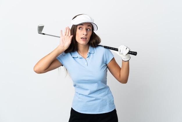 Młoda kobieta golfista na pojedyncze białe tło słuchając czegoś, kładąc rękę na uchu