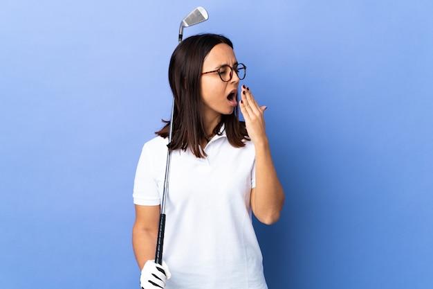 Młoda kobieta golfista na pojedyncze kolorowe ściany ziewanie i obejmujące szeroko otwarte usta ręką