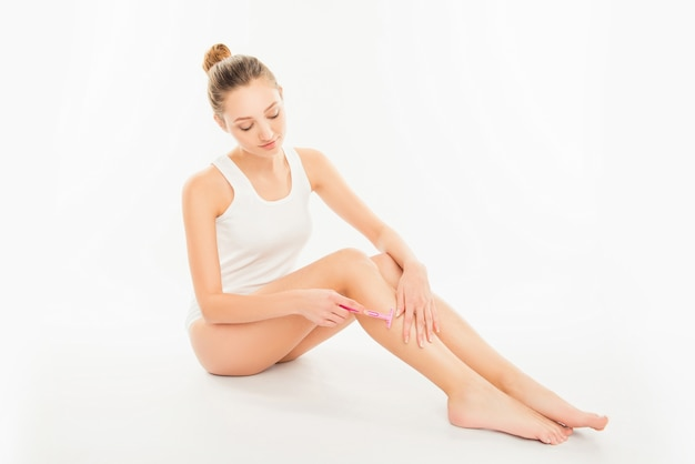 Młoda kobieta goli nogę