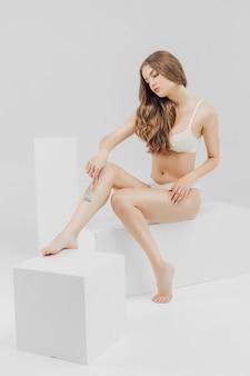 Młoda kobieta goli nogi, aby uzyskać gładką skórę