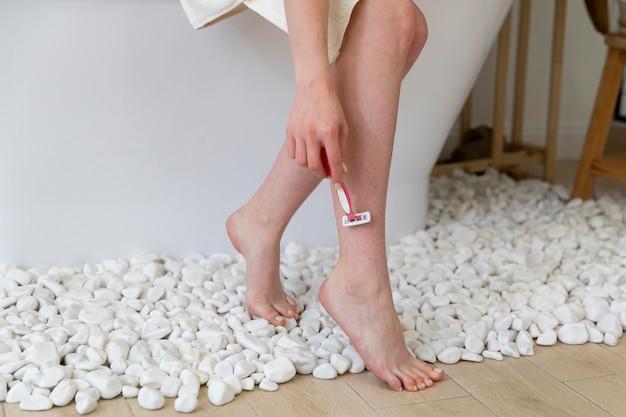 Młoda kobieta goli nogi