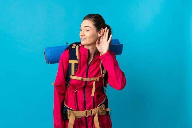 Młoda kobieta góral na odosobnionym niebieskim tle słuchając czegoś, kładąc rękę na uchu