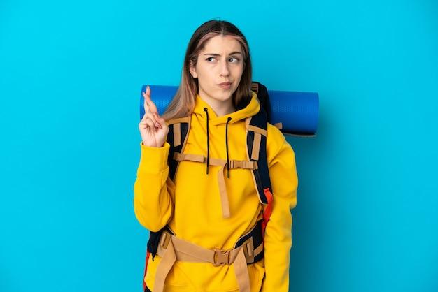 Młoda kobieta góral z dużym plecakiem na białym tle na niebiesko z palcami krzyżującymi się i życząc wszystkiego najlepszego