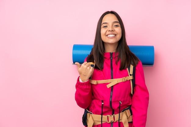 Młoda kobieta góral z dużym plecakiem na na białym tle różowy, wskazując na bok, aby przedstawić produkt