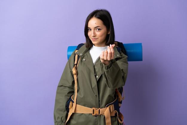 Młoda kobieta góral z dużym plecakiem na odizolowanej ścianie, dzięki czemu pieniądze gest
