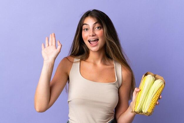Młoda kobieta gospodarstwa kukurydzy na białym tle na fioletowej ścianie salutowania ręką z happy wypowiedzi
