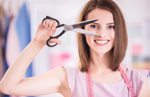 Młoda kobieta gospodarstwa nożyczki i patrząc na kamery.