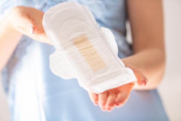 Młoda kobieta gospodarstwa podkładka menstruacyjna. podpaska higieniczna i koncepcja higieny kobiet.