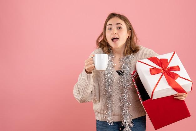Młoda kobieta gospodarstwa prezent świąteczny pudełko i filiżankę herbaty na różowo