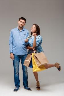 Młoda kobieta gospodarstwa zakupów, biorąc ostatnie pieniądze od mężczyzny