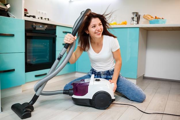 Młoda kobieta gospodyni bawi się odkurzaczem. zabawne sprzątanie mieszkania
