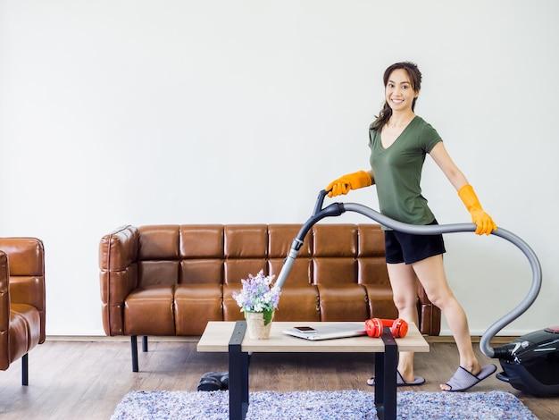Młoda kobieta, gospodyni domowa w zwykłych ubraniach i pomarańczowych gumowych rękawiczkach za pomocą odkurzacza do czyszczenia podłogi w salonie w pobliżu brązowej skórzanej sofy i stołu na białej ścianie z miejscem na kopię.