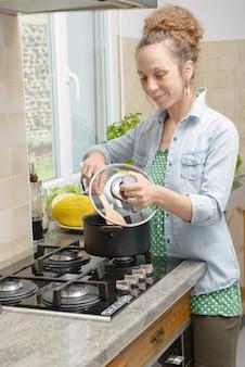 Młoda kobieta gotowania obiad w kuchni