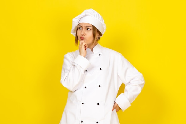 Młoda kobieta gotowania w białym garniturze gotować i białą czapkę myślenia wyrażenie