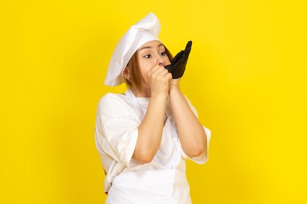 Młoda kobieta gotowania w białym garniturze i białej czapce na sobie czarne rękawiczki