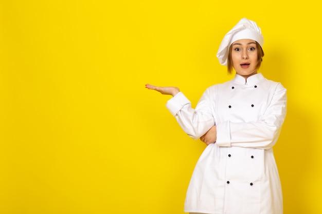 Młoda kobieta gotowania w białym garniturze i białej czapce uśmiecha się zaskoczony