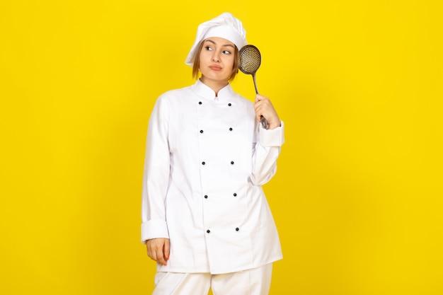 Młoda kobieta gotowania w białym garniturze kucharza i białej czapce pozowanie do myślenia trzymając srebrną łyżkę