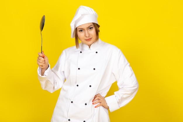 Młoda kobieta gotowania w białym garniturze kucharza i białej czapce stwarzających myślenia gospodarstwa srebrną łyżeczkę gniewne zagrożenie