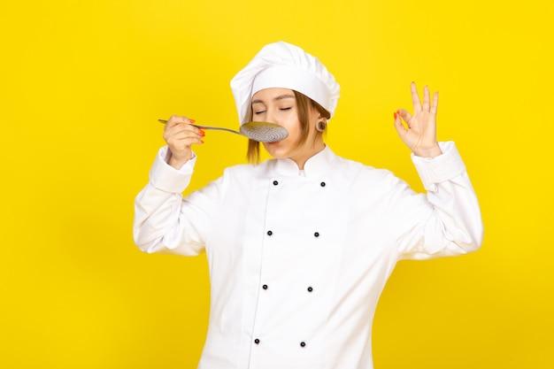Młoda kobieta gotowania w białym garniturze kucharza i białej czapce stwarzających myślenie trzymając srebrną łyżkę degustację