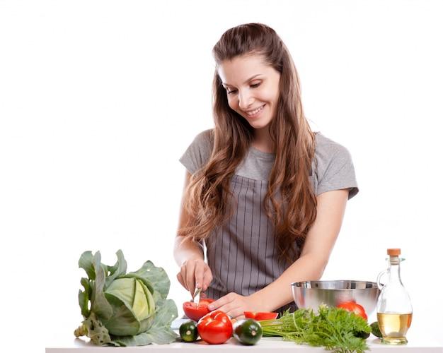 Młoda kobieta gotowania w kuchni. zdrowa żywność - sałatka jarzynowa.