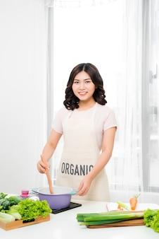Młoda kobieta gotowania w kuchni. zdrowe jedzenie. koncepcja diety. zdrowy tryb życia. gotowanie w domu. przygotuj jedzenie