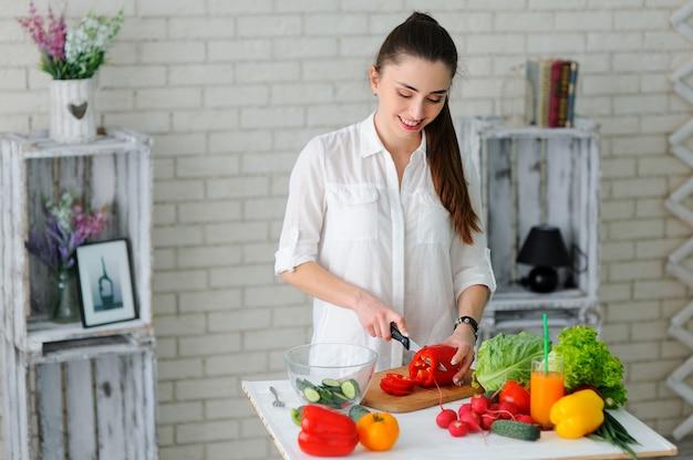 Młoda kobieta gotowania. zdrowa żywność - sałatka jarzynowa. dieta. zdrowy tryb życia. gotowanie w domu. przygotuj jedzenie