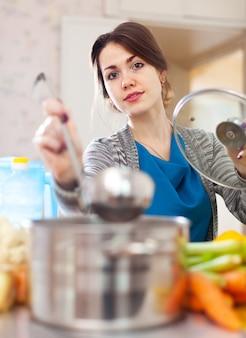 Młoda kobieta gotowanie zupy z laddle