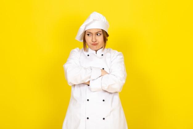Młoda kobieta gotująca w białym garniturze kucharza i białej czapce szalony niezadowolony wyraz