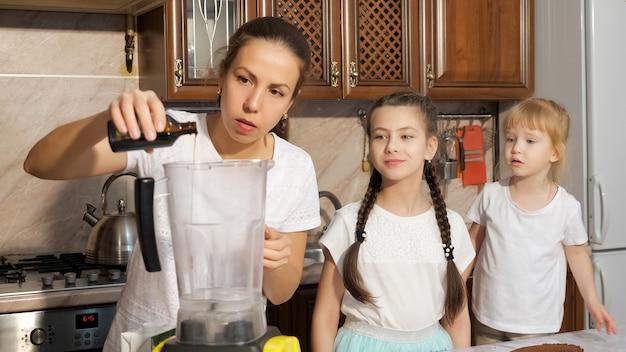 Młoda kobieta gotuje śmietankę do ciasta nalewając syrop i dodając nerkowce w blenderze z córkami w kuchni w domu. rodzinne gotowanie z mamą.