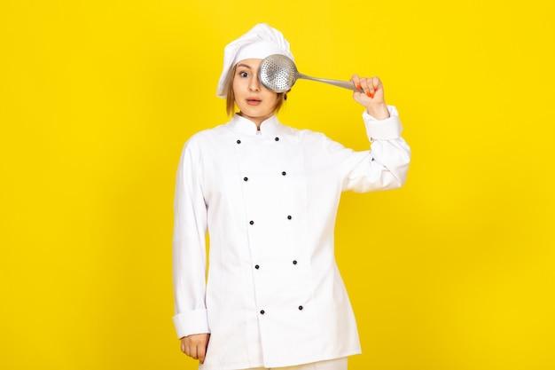 Młoda kobieta gotuje w białym garniturze i białej czapce, myśląc, że trzyma srebrną łyżeczkę zasłaniającą jej oko