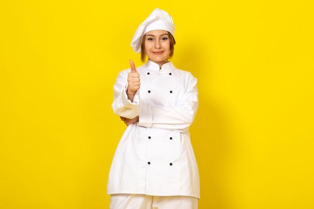 Młoda kobieta gotuje w białym garniturze i białej czapce uśmiecha się