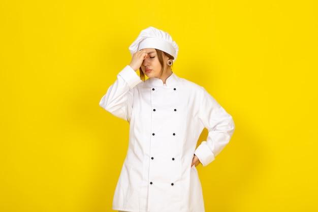 Młoda kobieta gotuje w białym garniturze i białej czapce zmęczona, odczuwając silny ból głowy