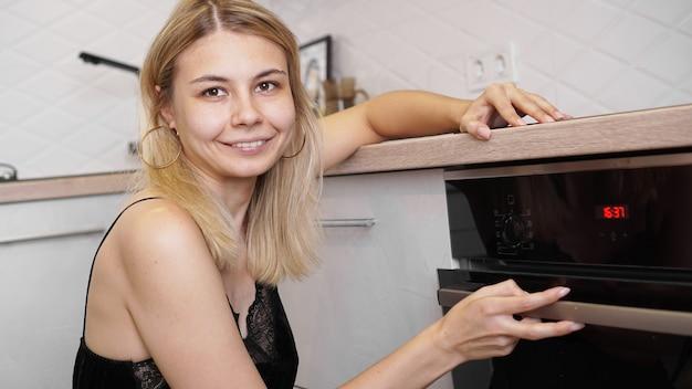 Młoda kobieta gotuje w kuchni otwierając drzwi piekarnika