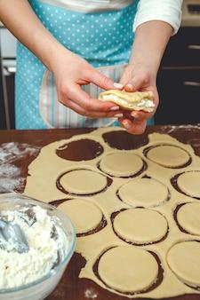Młoda kobieta gotuje w kuchni, przygotowuje ciasto do pieczenia, dodaje do ciasta farsz z twarogu