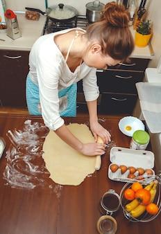 Młoda kobieta gotuje w kuchni, zwija ciasto wałkiem do pieczenia na stole