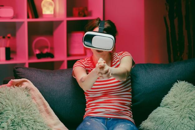 Młoda kobieta gra i uśmiecha się w zestawie vr. kask rzeczywistości wirtualnej na kolorowym oświetleniu