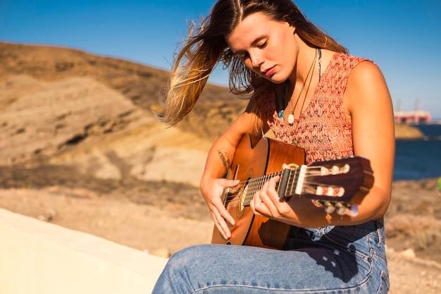 Młoda kobieta gra na gitarze akustycznej na świeżym powietrzu.