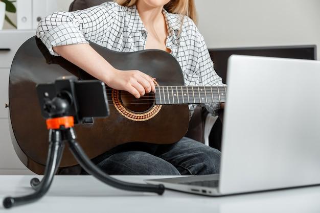 Młoda kobieta gra na gitarze akustycznej w domu dla odbiorców online na laptopie i smartfonie. zajęcia online to kursy gry na gitarze e edukacja w czasie blokady. gra na gitarze muzycznej online.