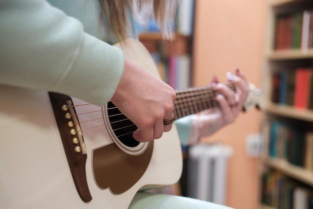 Młoda kobieta gra na gitarze akustycznej. zbliżenie bez twarzy