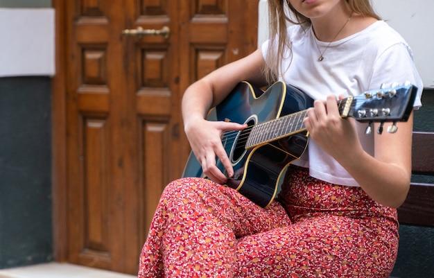 Młoda kobieta gra na gitarze na ulicy