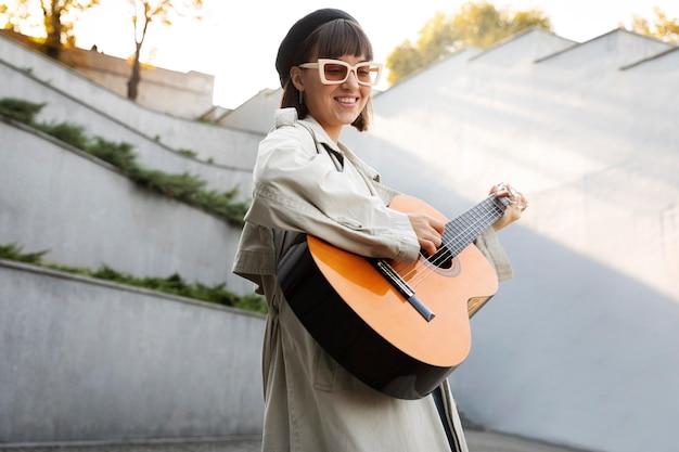 Młoda kobieta gra na gitarze na zewnątrz