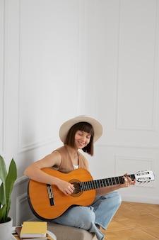 Młoda kobieta gra na gitarze w pomieszczeniu z miejscem na kopię