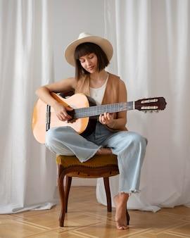 Młoda kobieta gra na gitarze w pomieszczeniu