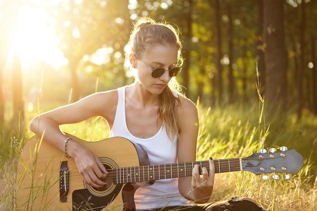 Młoda kobieta gra na gitarze w przyrodzie podczas zachodu słońca